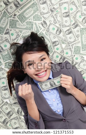 successful business woman hold fist with money and lying on money bed, asian beauty model - stock photo