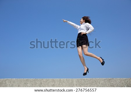 Successful business woman jump and finger pointing something with blue sky background, full length, asian - stock photo