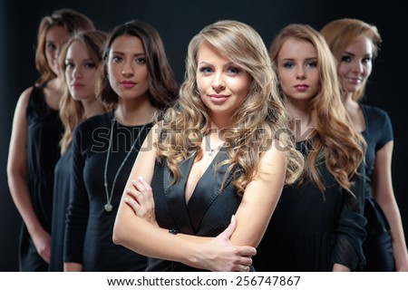 Successful business woman leading a team. Confident young woman with long hair standing with arms folded and her friends smiling from her back against black background. - stock photo
