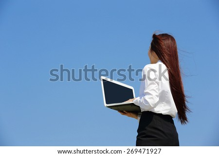 Successful business woman purposefully looking away and hold a computer with blue sky, asian beauty - stock photo