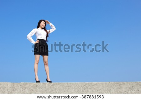 Successful business woman purposefully looking away with blue sky, asian beauty - stock photo
