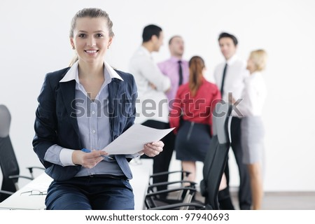 Successful business woman standing with her staff in background at modern bright office - stock photo