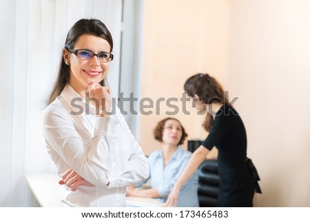 Successful business woman standing with her staff in background at office - stock photo