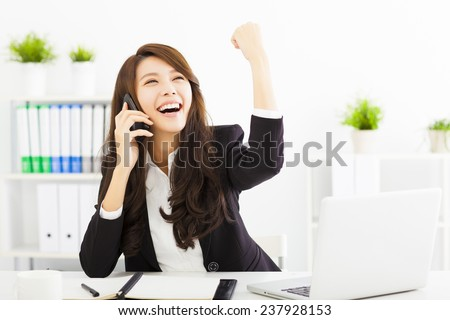 successful business woman talking on the phone in office - stock photo