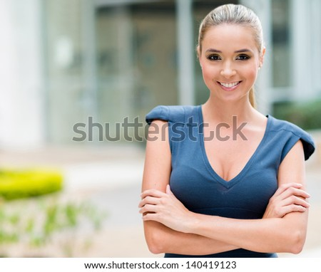 Successful business woman with arms crossed smiling - stock photo