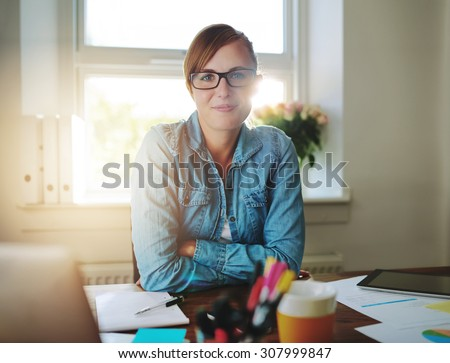 Successful business woman working at the office looking at camera - stock photo