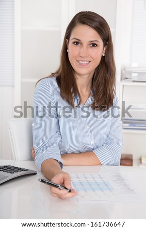 Successful business: young woman in blue blouse sitting at desk smiling and holding pen - stock photo