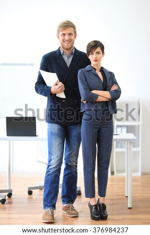 Successful businessman and businesswoman standing with documents in the office. Team work concept - stock photo