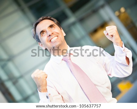 Successful businessman celebrating his triumph looking very happy - stock photo