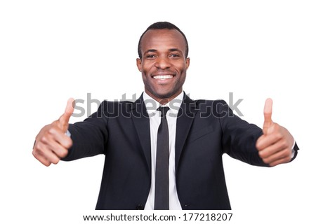 Successful businessman. Cheerful young African man in formalwear showing his thumbs up and smiling while standing isolated on white background  - stock photo