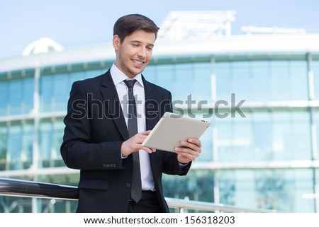 Successful businessman. Cheerful young men in formalwear holding digital tablet and smiling - stock photo