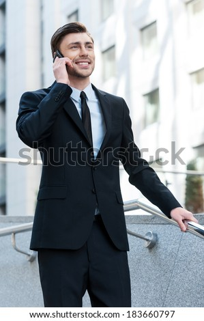 Successful businessman. Cheerful young men in formalwear talking on the mobile phone while going downstairs - stock photo