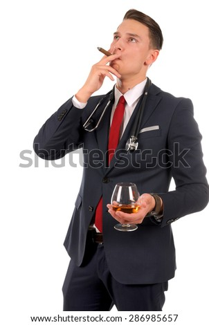 Successful businessman drinking whisky and smoking a cigar - stock photo