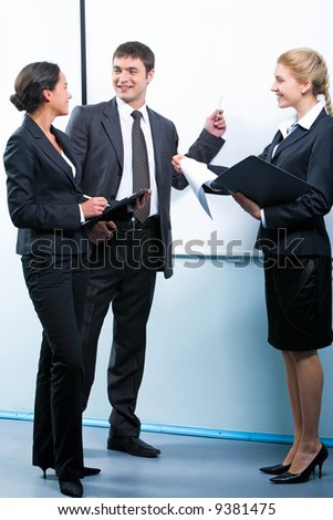 Successful businessman explaining business plan to one of his colleagues pointing at a board - stock photo