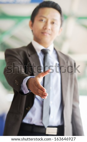 Successful businessman giving a hand - stock photo
