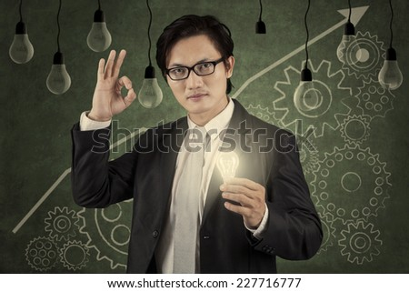 Successful businessman holding a bright lightbulb in front of  upward graph - stock photo