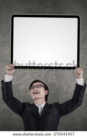 Successful businessman in business suit, lifting an empty signboard - stock photo