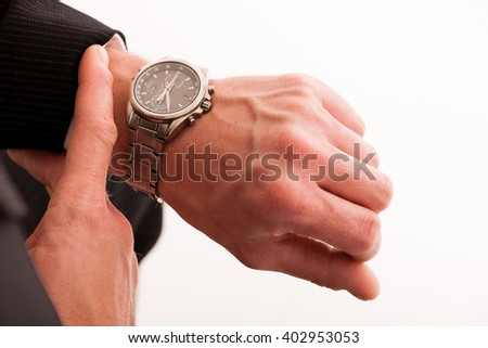 Successful businessman in formal suit checking time on wrist watch isolated over white. - stock photo