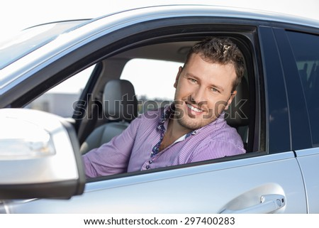 Successful businessman is sitting at steering wheel of his car. He is smiling and looking at the camera through window - stock photo