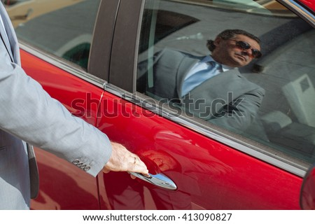 Successful businessman opens its luxury car red. Portrait of a serious man on glass window of the car. - stock photo