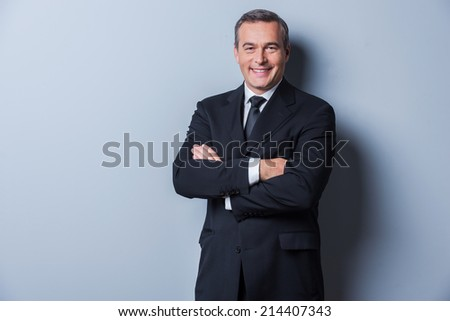 Successful businessman. Portrait of confident mature man in formalwear looking at camera and smiling while keeping arms crossed and standing against grey background - stock photo