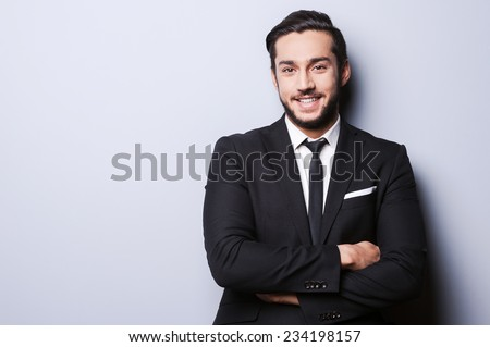 Successful businessman. Portrait of confident young man in formalwear looking at camera and smiling while keeping arms crossed and standing against grey background - stock photo