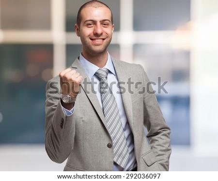 Successful businessman raising his fist - stock photo
