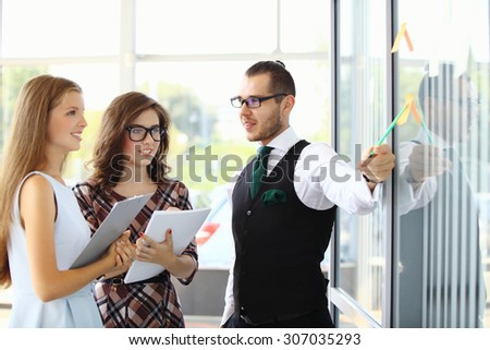 Successful businessman reading lecture to his colleagues at presentation of new project - stock photo