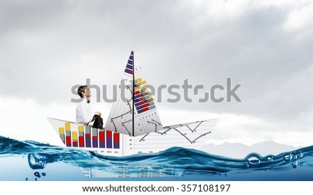 Successful businessman sailing on paper boat in financial sea - stock photo