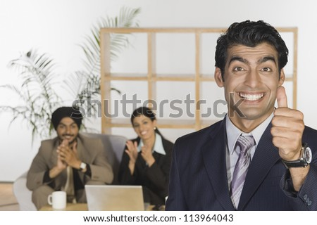 Successful businessman showing thumbs up sign - stock photo