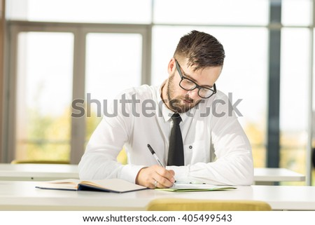 Successful businessman sitting in an office and writing some notes in his planner - stock photo
