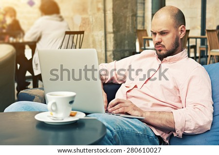 Successful businessman sitting on sofa front open laptop computer and cup of coffee or tea, young freelancer work on notebook in modern coffee shop or hotel interior, make money on-line, e-business - stock photo
