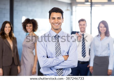 Successful businessman smiling at camera with his arms crossed and his colleagues posing in background - stock photo