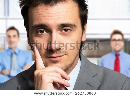 Successful businessman standing in front of his colleagues - stock photo