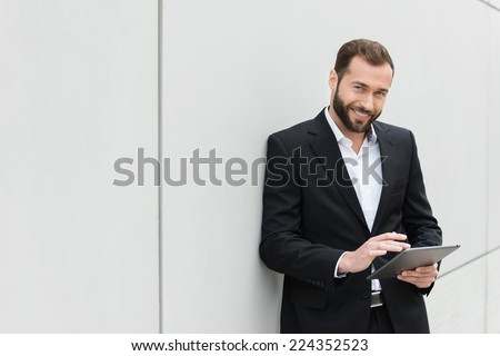 Successful businessman standing using a tablet to access the internet as he leans against a white wall with copyspace - stock photo