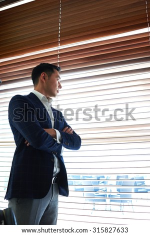Successful businessman with crossed arms thinking about something while standing near window with a venetian blinds, thoughtful men entrepreneur dressed in suit resting after meeting with partners - stock photo