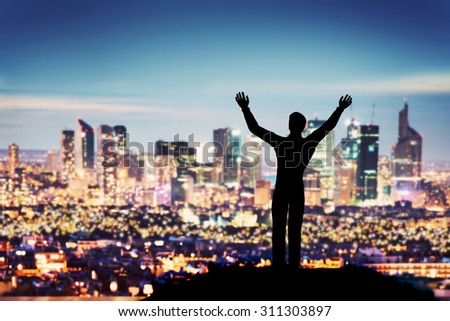 Successful businessman with hands up facing city business downtown at night. Concept of winner, corporate manager etc. - stock photo