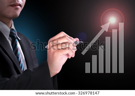 successful businessman writing haft year profit with magic pen presenting up level every month with blasting flare high light and business growth blue light background - stock photo