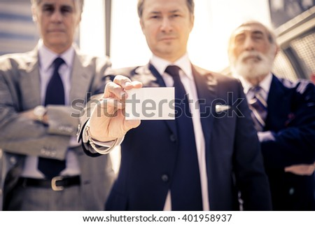Successful businessmen holding a blank business card - Three mature business men in the background, white empty card for text - stock photo