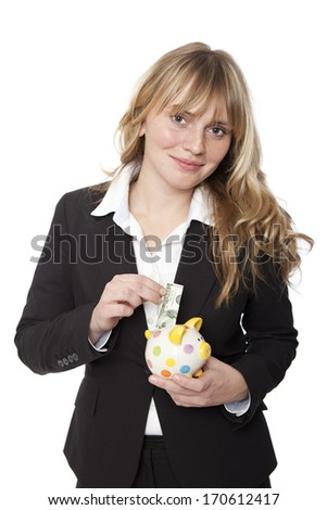 Successful businesswoman banking her money in a cute yellow polka dot piggy bank with a smile inserting a banknote in the slot, isolated on white - stock photo
