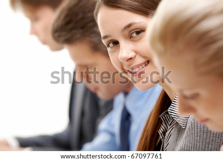 Successful businesswoman between partners looking at camera - stock photo