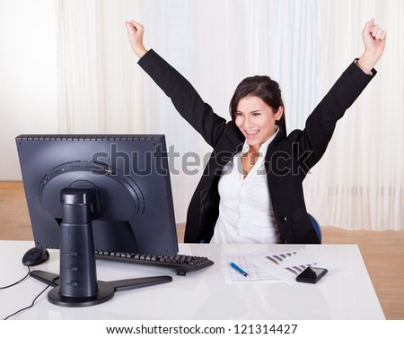 Successful businesswoman celebrating by throwing her arms up on the air as she sits back in her office chair and looks at her computer screen - stock photo
