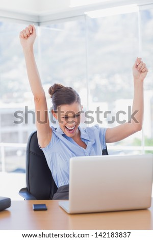 Successful businesswoman cheering in the office - stock photo