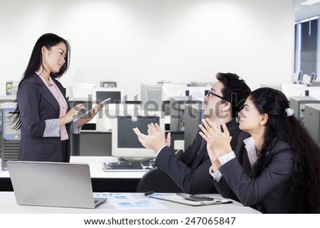 Successful businesswoman get applause from her partners after presentation in the office - stock photo