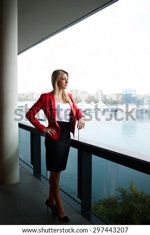 Successful businesswoman in corporate clothing standing on the balcony terrace with beautiful marina view while relaxing the open air, confident female entrepreneur thoughtfully look into the distance - stock photo