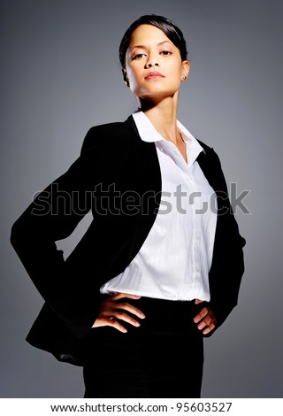Successful businesswoman in suit with her hands on her hips - stock photo