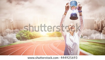 Successful businesswoman lifting a trophy against composite image of racetrack in city - stock photo
