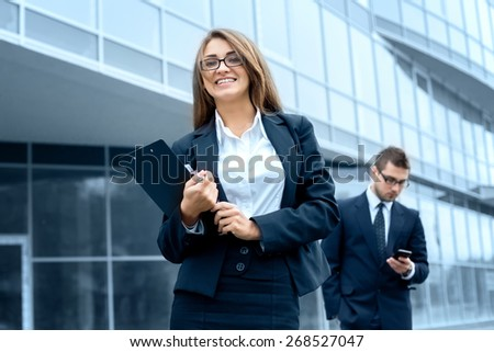 Successful businesswoman or entrepreneur using a digital tablet computer, standing in front of his office. - stock photo