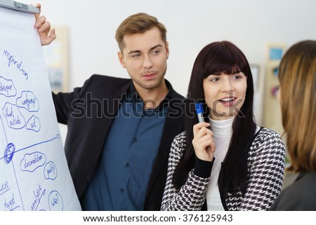 Successful businesswoman or manageress standing discussing a flow chart with her business team or colleagues, close up view - stock photo