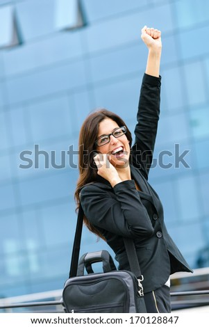 Successful businesswoman raising arm while talking on cellphone and walking outdoor in city street. Female winner executive success in business. - stock photo